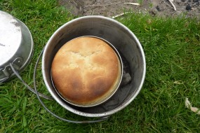 Baking bread in billy cans - note tiffin tin inside billy can and green stick supporting it!
