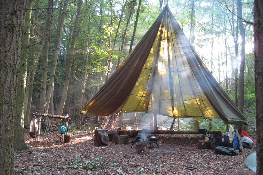 Bushcraft camp, kettle on the go under the parachute