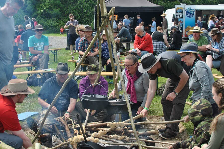 Bushcraft show visitors baking bread and bannock