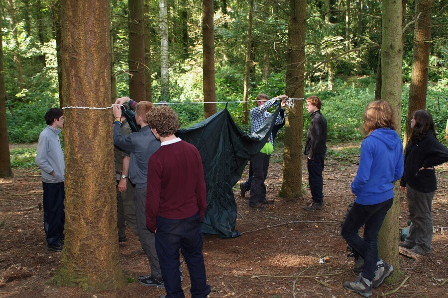 Explorer Scouts learning how to set up a tarp and hammock