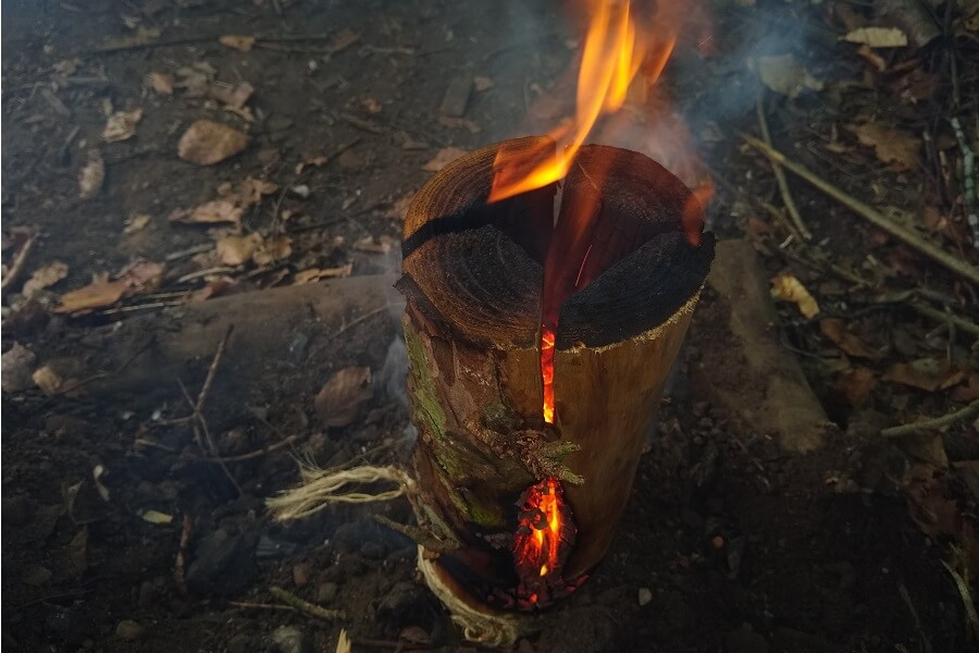 Embers glowing through the gaps of the rocket stove