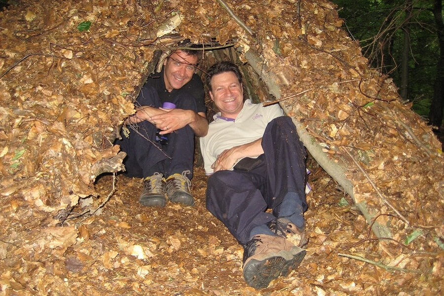 Scout leaders relax in their natural shelter